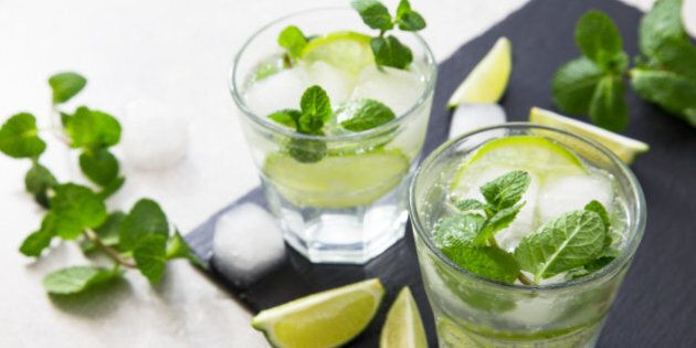 Cold refreshing summer lemonade mojito in a glass on a slate board and stone