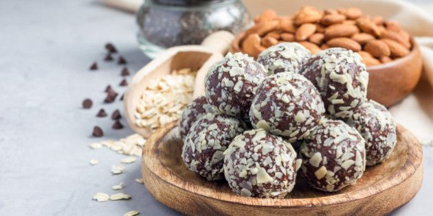 Healthy homemade paleo chocolate energy balls with rolled oats, nuts, dates and chia seeds, horizontal, copy space