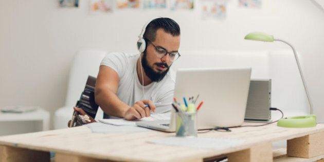 Man with acoustic guitar composing music for iStock and Getty stock library. Using laptop and writing lyrics or music notes. Wearing headphones around neck and typing on laptop.