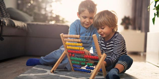 Little boy is helping his little brother to learn counting on abacus. Sunny