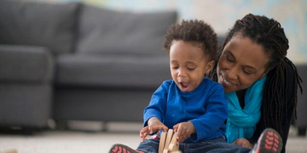 A mother is playing with her little boy in their home on mother's day. The toddler is playing with wooden...
