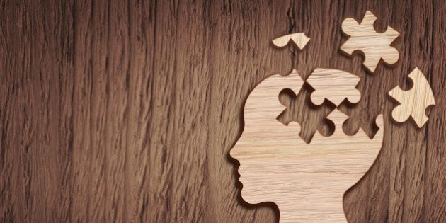 Human head silhouette with a jigsaw piece cut out on the wooden background, mental health