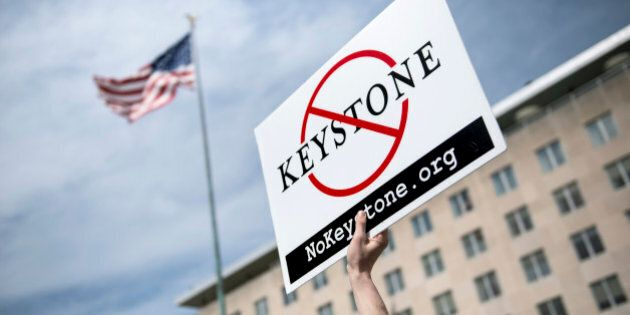 An activist holds up a sign outside the State Department during a protest of the Keystone XL pipeline...