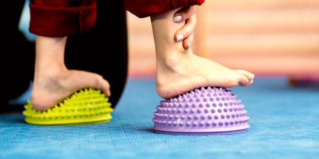 Flat Feet Corrective Exercises - Little boy walking over spikey half balance rubber balls on a physical...