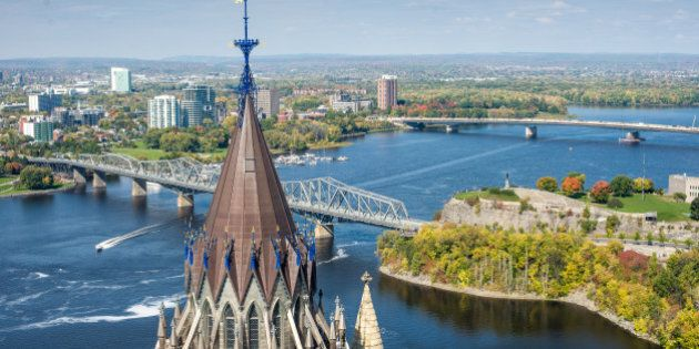 The spire of the Parliamentary Library is in the foreground and the Interprovincial and McDonald-Cartier bridges are in the background, joining Ontario and Quebec across the Ottawa River in downtown Ottawa and Gatineau.