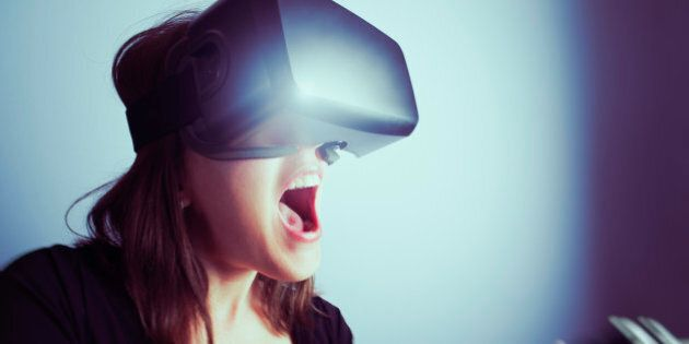 A mid-adult woman wearing a virtual reality headset, using a video game controller, totally involved...