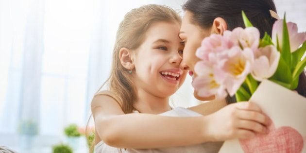 Happy mother's day! Child daughter congratulates mom and gives her flowers tulips and postcard. Mum and...
