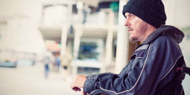 Homeless young invalid man sitting in wheelchair on the
