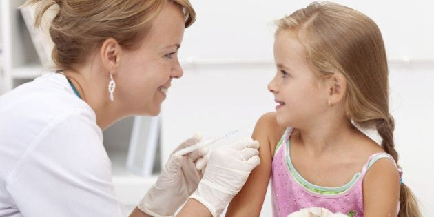 Brave little girl receiving injection or vaccine with a