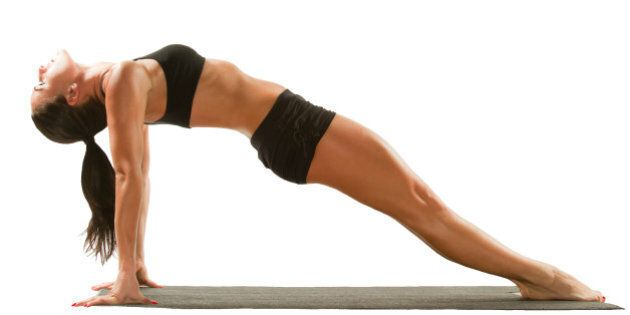 Sexy young yoga female doing yogic exercise on isolated white