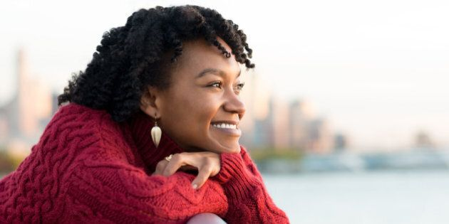 Close up portrait of a young happy african woman leaning on the banister of a bridge near river. Happy...