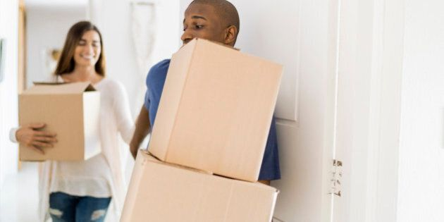 Young man and woman with cardboard boxes at doorway. Multi-ethnic couple are moving into new apartment....