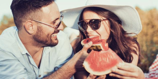 Young couple on a picnic together bite a one piece of watermelon.