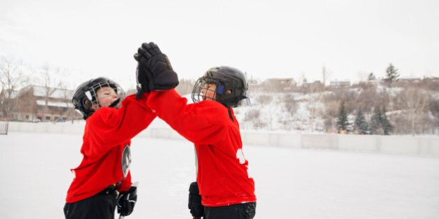 Ice hockey players giving high-five on