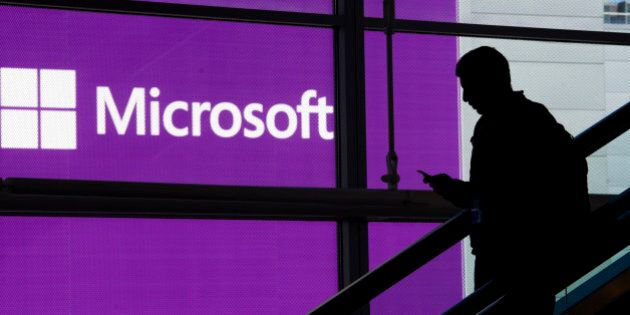 An attendee is silhouetted against a Microsoft Corp. poster as he rides an escalator at the Microsoft...