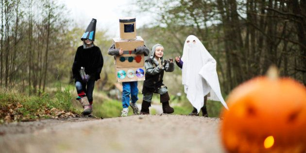 Children (4-12) wearing fancy dress costumes on country lane, carved pumpkin in