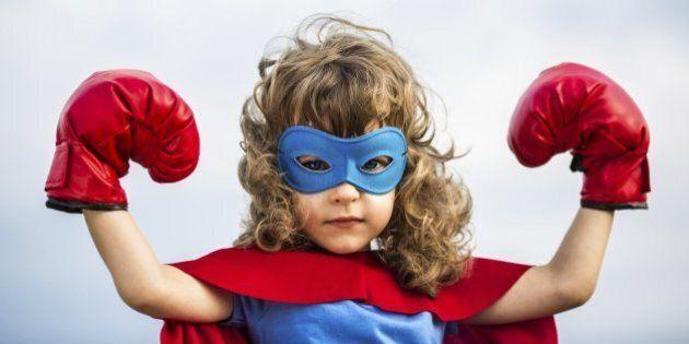 Superhero kid wearing boxing gloves against blue sky background. Girl power and feminism