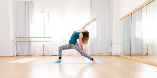 Young woman doing high lunge yoga asana in light spacious studio, virabhadrasana