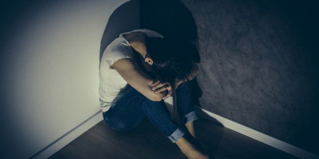 Woman victim of domestic violence and abuse sitting in acorner of a room frightened