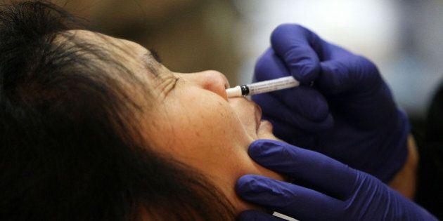 SAN FRANCISCO - DECEMBER 22: A woman receives an H1N1 flu nasal spray vaccination during a clinic at...