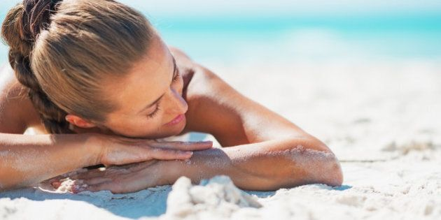 Happy young woman in swimsuit relaxing while laying on sandy