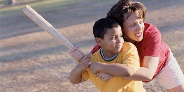 Mother helping son sing a baseball bat