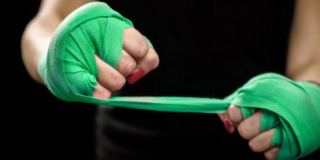 Woman is wrapping hands with green boxing wraps. Isolated on black with red nails. Strong hand and fist,...