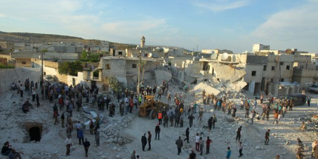 Residents inspect a site damaged by an airstrike in Hafsarja, in the insurgent stronghold of Idlib province,...