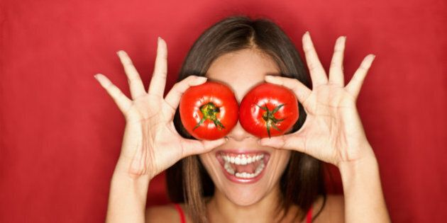 Tomato. Woman showing tomatoes holding them in front of eyes. Fresh energetic funny image on red background. See more