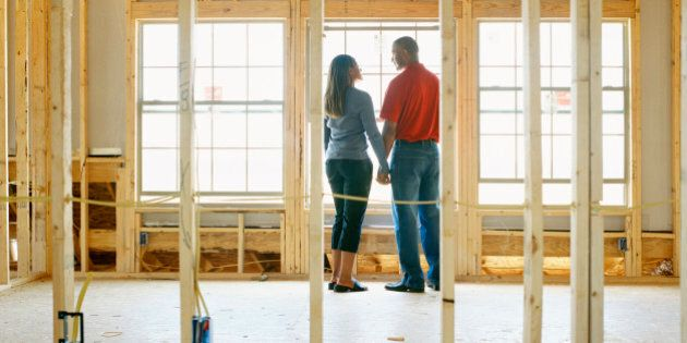 Couple holding hands in home under construction, rear
