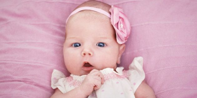 Cute beautiful newborn baby girl on a pink blanket inbeautiful tiny dress and a pink flower hairband...