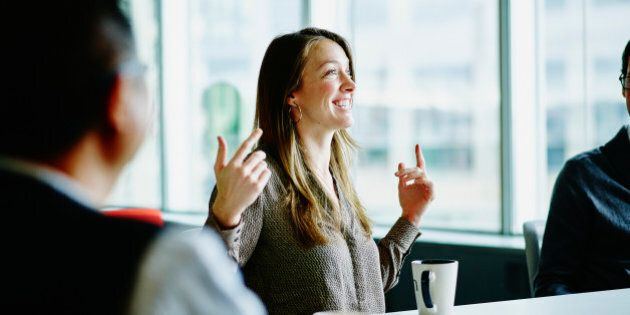 Smiling businesswoman leading project discussion during meeting with coworkers at office conference room