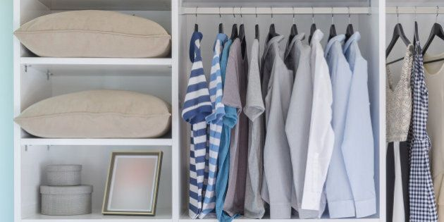 clothes hanging in white wardrobe with pillows and