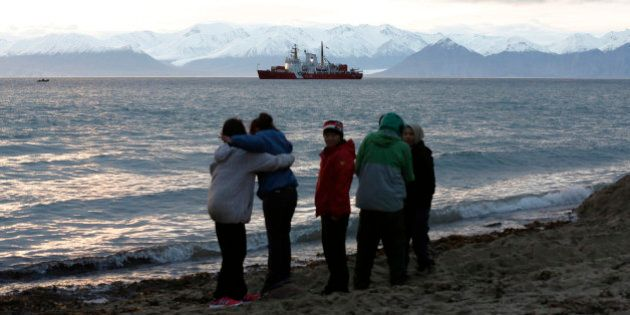 Local children stand on the shore as the Coast Guard ship Des Groseilliers sits in the waters near the...
