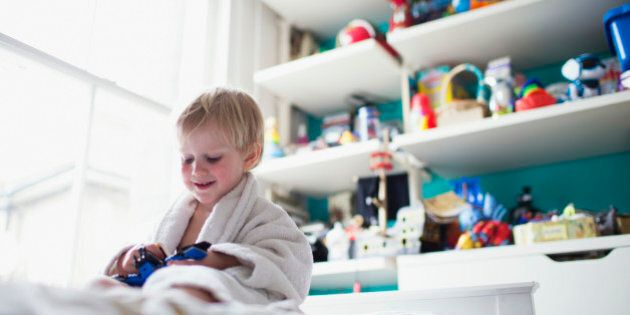 Boy sitting in bed in his room playing with toy