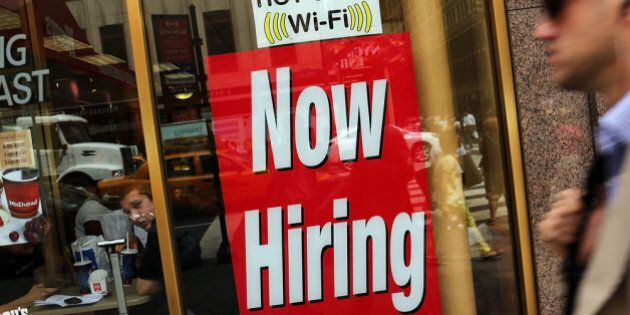 NEW YORK, NY - AUGUST 07: A 'now hiring' sign is viewed in the window of a fast food restaurant on August...