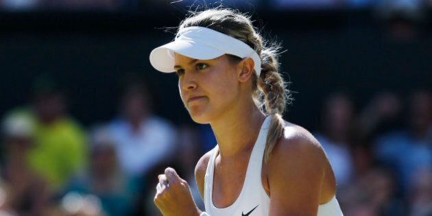 Eugenie Bouchard of Canada celebrates after winning the first set as she plays against Simona Halep of...
