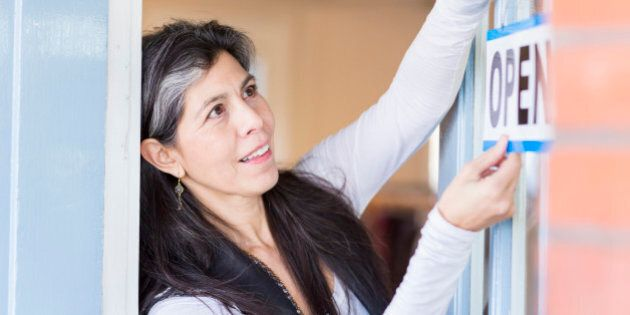 Hispanic small business owner hanging open sign on
