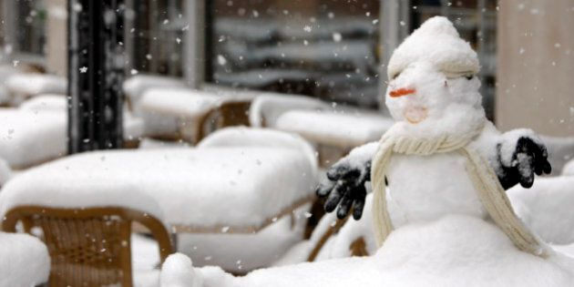 A snowman sits on a snow-covered table on the patio of a downtown Denver eatery as an autumn snowstorm...
