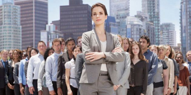 Portrait of confident businesswoman with business people in background