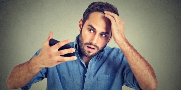 Closeup portrait, shocked man feeling head, surprised he is losing hair, receding hairline, bad news isolated on gray wall background. Negative facial expressions, emotion feeling