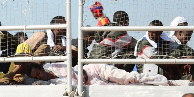Migrants wait to disembark from the Migrant Offshore Aid Station vessel ' Phoenix ' in the harbor of...