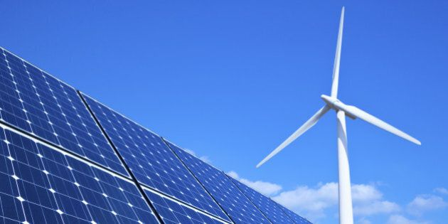 Solar panels and wind turbine against blue