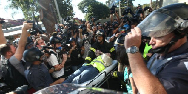 SAO PAULO, BRAZIL - JUNE 12: A journalist is taken from a protest on a stretcher outside Carrao Metro...