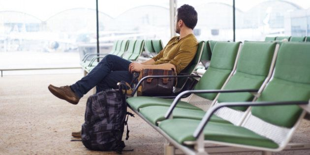 Young man is waiting at the airport for his flight