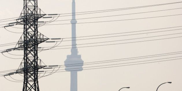 Hydro One power lines cover the view of the CN tower, along with heavy smog, east of downtown Tuesday afternoon. (Photo by Lucas Oleniuk/Toronto Star via Getty Images)