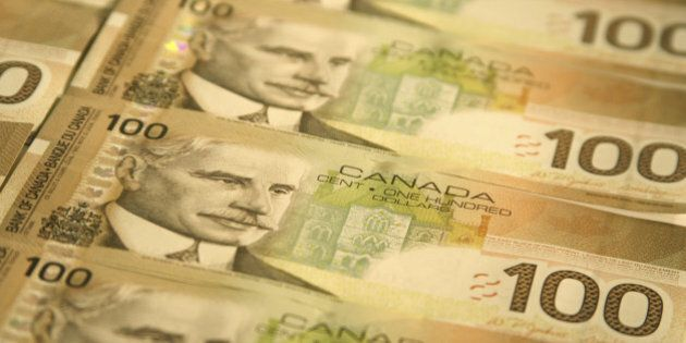 'A group of Canadian $100 bills lined up in rows. Focus is on the face of Prime Minister Robert Borden...