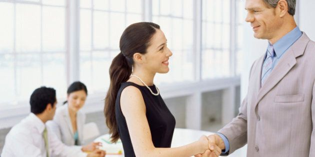 side profile of a businesswoman and a businessman shaking hands