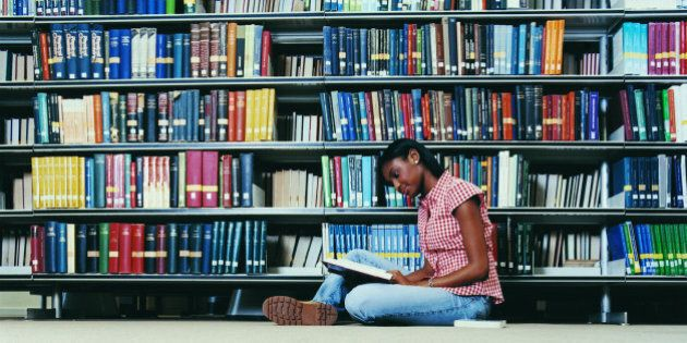 Female University Student Sitting on a Library Floor Reading a