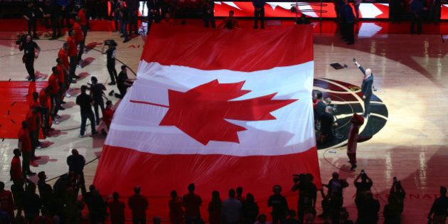 TORONTO, CANADA - APRIL 16: A large Canadian flag is unfurled during the singing of O Canada before the...